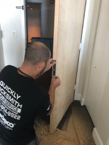 Our locksmith technician installing a brand new door in a residential building in Miami FL