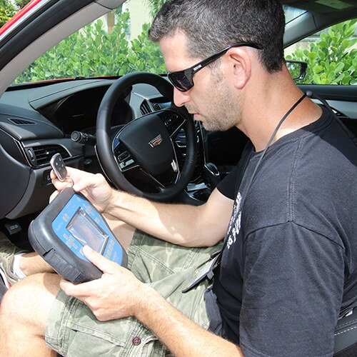 Car locksmith technician on work, trans-coding a new set of keys for a client in Miami FL