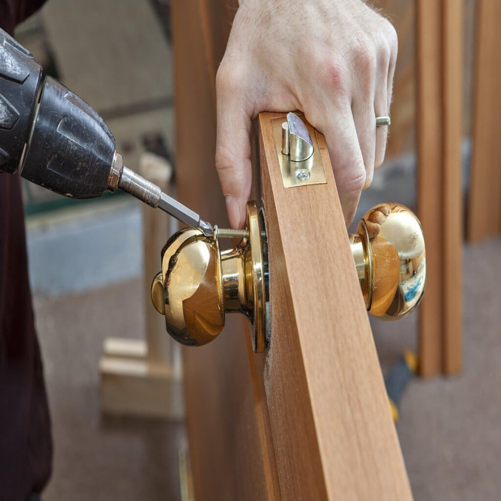 locksmith technician prepares the door for installation at a condo in Miami FL